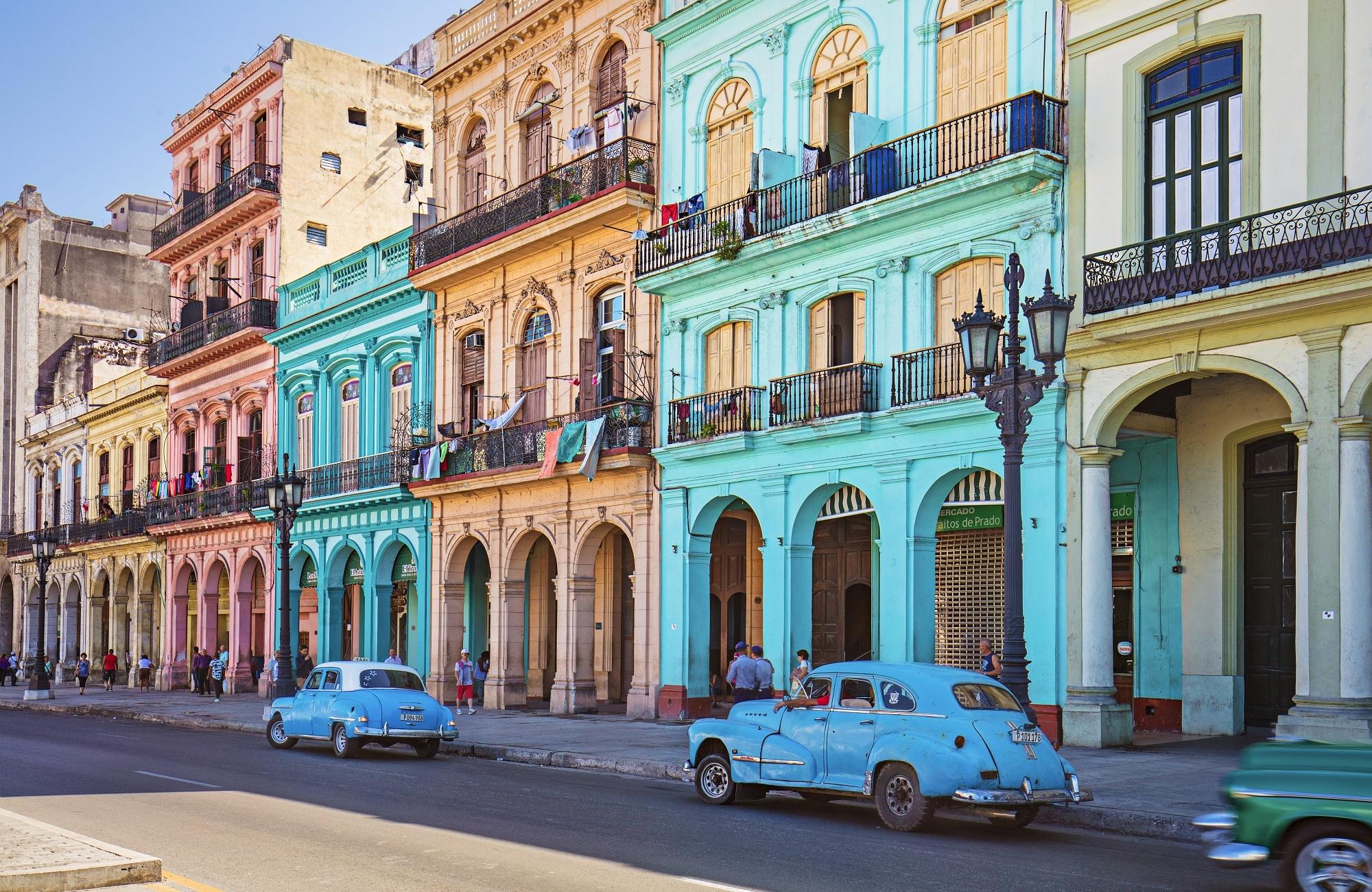 Voitures vintages garées face aux bâtiments colores historiques de La Havane