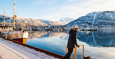 Teenage noy outdoors on winter day enjoying views of Tromso Norway