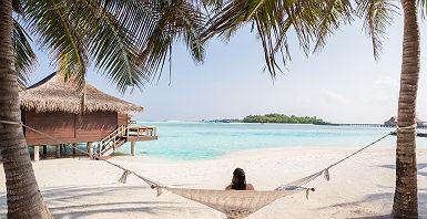 Polynésie - Portrait d'une touriste qui se repose sur une hamac avec vue sur un bungalow sur pilotis dans les eaux turquoises de Tahiti