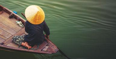 Vietnam - Portrait d'une femme qui rame dans son bateau sur le Mékong