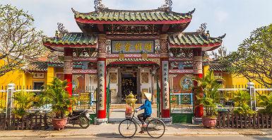 Vietnam - Portrait d'une femme locale en vélo devant la salle de l'assemblée Trieu Chau à Hoi An