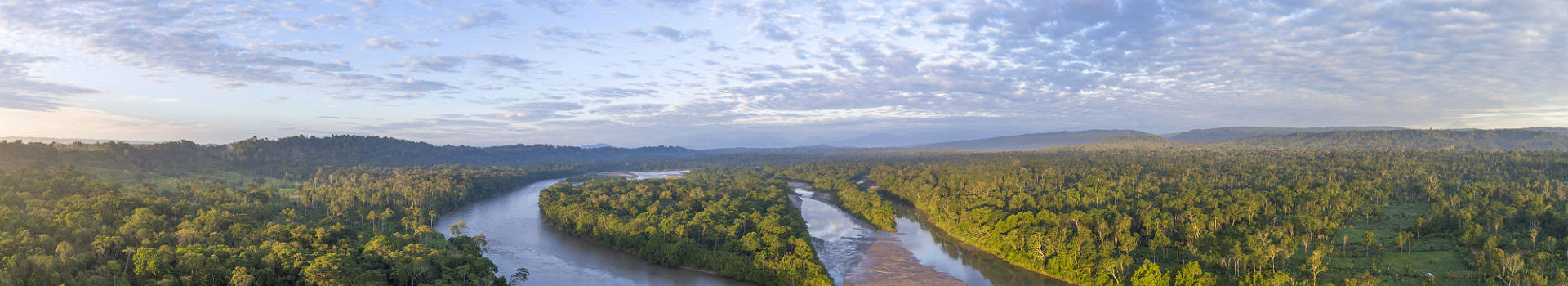 Aerial panorama of the Rio Napo at dawn in the Ecuadorian Amazon with the first rays of the sun illuminating the forest canopy